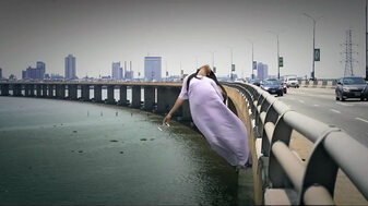 God Calling production still: Zainab Balogun plunging into Lagos lagoon from Third Mainland Bridge