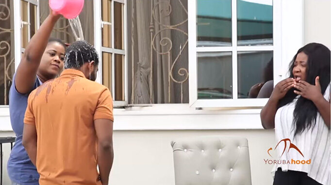 Latana production still Seun Omojola pouring water on Gabriel Afolayan, while Goodness Usman watched in shock