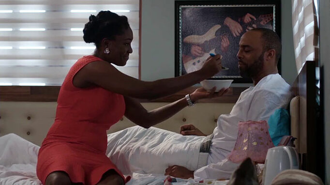 The Kinsman production still: Lota Chukwu spoon feeding Kalu Ikeagwu